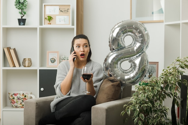 ワインのガラスを保持している幸せな女性の日に混乱している側の美しい女性は、リビングルームの肘掛け椅子に座っているワインについて話します