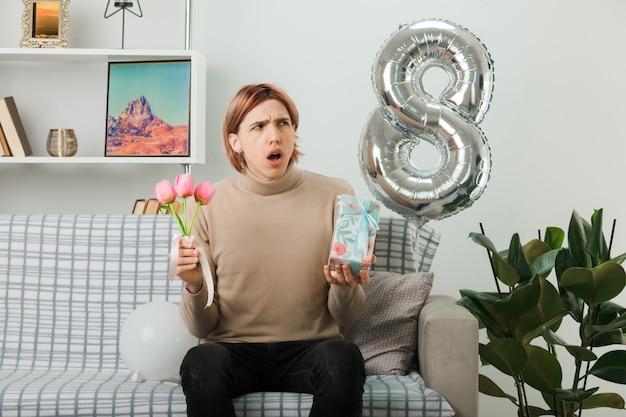 リビングルームのソファに座っているプレゼントと花を保持している幸せな女性の日に混乱して見える側のハンサムな男
