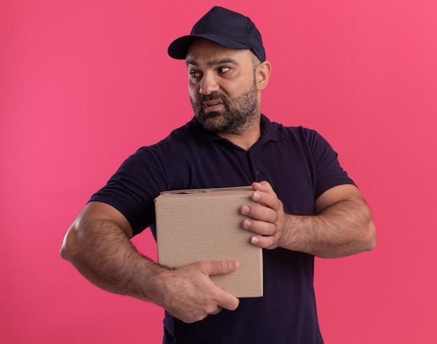 Confuso guardando il fattorino di mezza età laterale in uniforme e scatola di contenimento tappo isolato sulla parete rosa