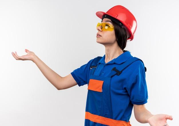 Смущенный глядя на сторону молодой женщины-строителя в униформе с очками, разводя руками