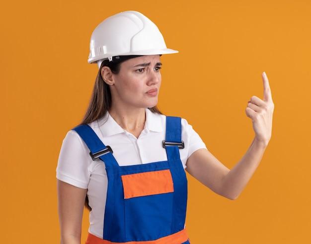 Confuso guardando lato giovane donna costruttore in punti uniformi in alto isolato sulla parete arancione