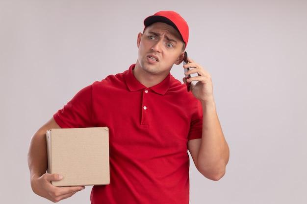 Confuso guardando a lato il giovane fattorino che indossa l'uniforme con la scatola di contenimento del cappuccio parla al telefono isolato sul muro bianco con spazio di copia
