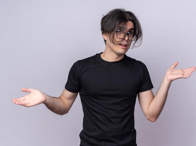 Guardando confuso il giovane bel ragazzo che indossa una maglietta nera e occhiali che allargano le mani isolate sul muro bianco