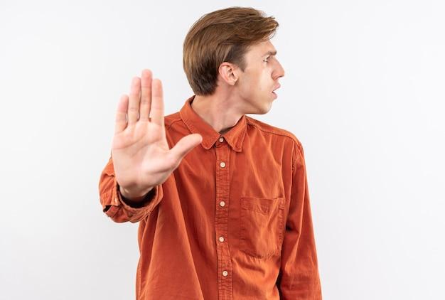 白い壁に分離された停止ジェスチャーを示す赤いシャツを着て混乱している側の若いハンサムな男
