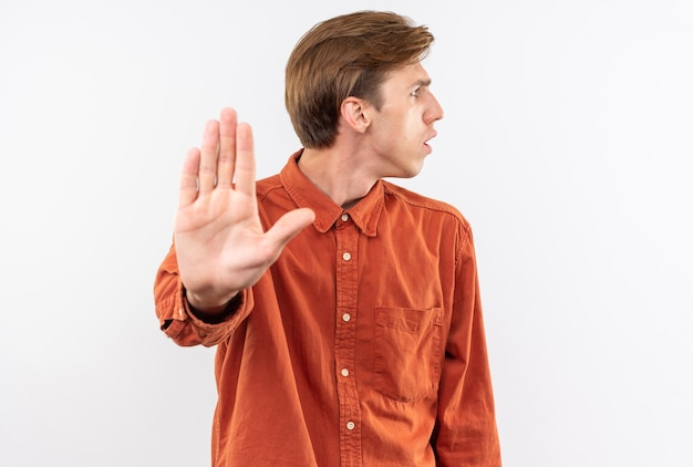 Confused looking side young handsome guy wearing red shirt showing stop gesture isolated on white wall