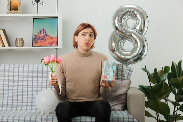 リビングルームのソファに座っているプレゼントと花を持って幸せな女性の日にハンサムな男を見上げる混乱