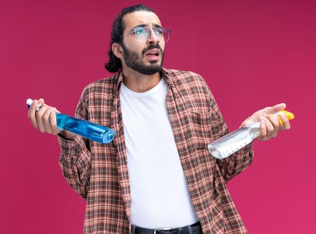 ピンクの壁に分離されたスプレーボトルを保持しているtシャツを着ている若いハンサムな掃除人を見上げる混乱