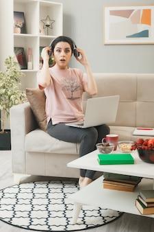 リビングルームのコーヒーテーブルの後ろのソファに座っているヘッドフォンを身に着けているラップトップで混乱しているように見える若い女の子