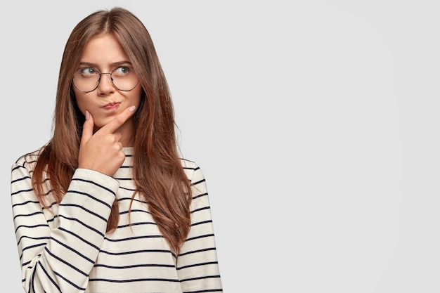 Смущенная милая девушка-подросток держит подбородок, задумчиво смотрит в сторону, у нее темные волосы, носит полосатый свитер, изолирована на белой стене