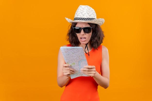 Una giovane donna adorabile confusa con i capelli corti in una camicia arancione che porta il cappello del sole e gli occhiali da sole che esaminano la mappa
