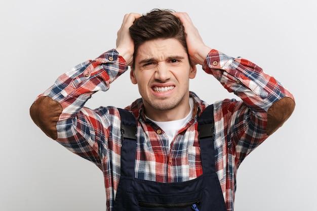 灰色の壁に頭を抱えている混乱の男性ビルダー
