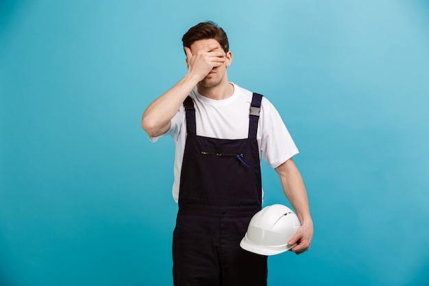 青い壁に目を覆っている間保護用のヘルメットを保持している混乱している男性ビルダー