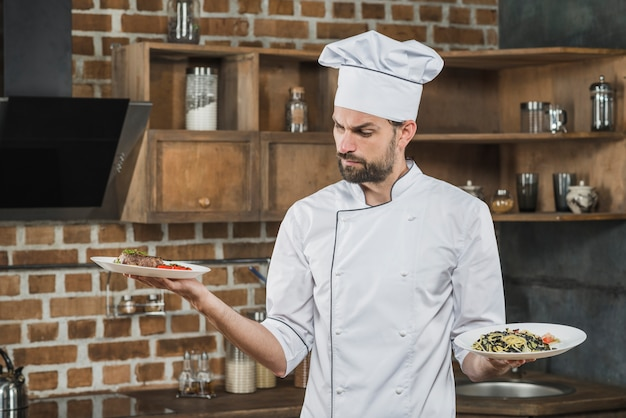 Confused male cook looking at prepared dishes