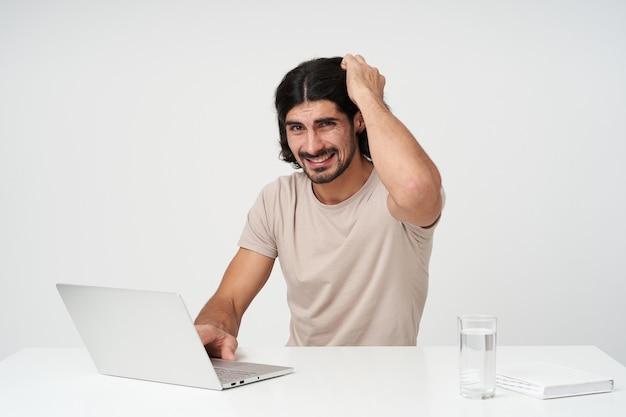 혼란 스 러 워 남성, 검은 머리카락과 수염을 가진 의심 사업가. 사무실 개념. 직장에 앉아. 랩톱에서 작업하면서 머리를 긁적입니다. 흰 벽 위에 절연