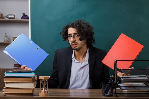 Insegnante maschio confuso con gli occhiali che tiene la cartella seduta al tavolo con gli strumenti della scuola in classe