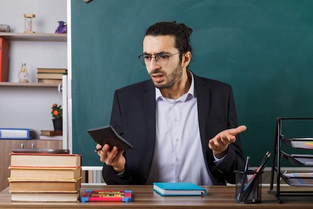 Insegnante maschio confuso che indossa gli occhiali che tiene e guarda la calcolatrice seduto al tavolo con gli strumenti della scuola in classe