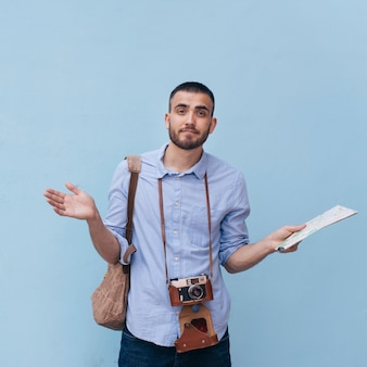 Confused male traveler shrugging his shoulder holding map standing against blue wall