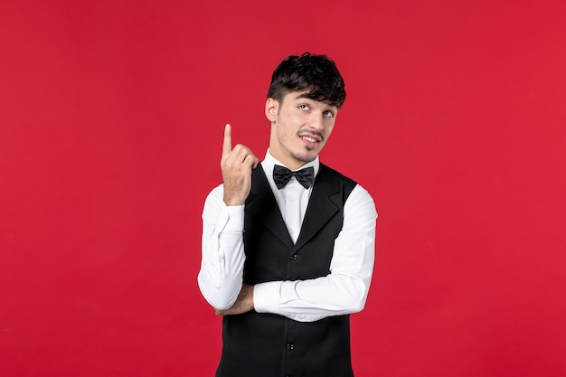 Confused male waiter in a uniform with butterfly on neck pointing up on red background
