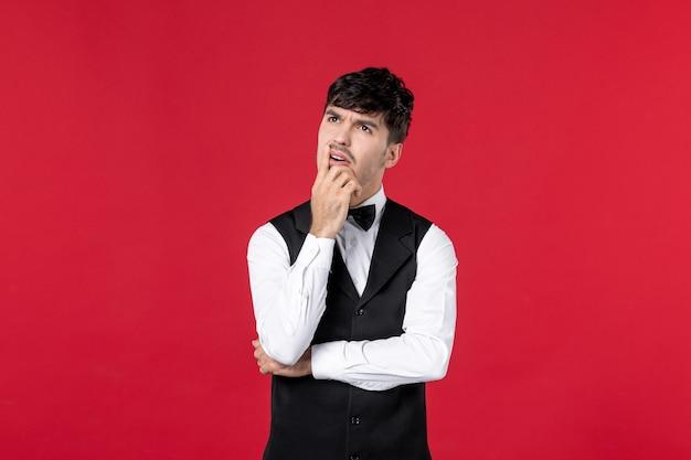 Cameriere maschio confuso in uniforme con farfalla sul collo su sfondo rosso