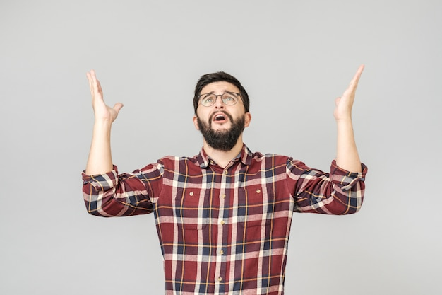Confused  man asking from heaven raising his hand
