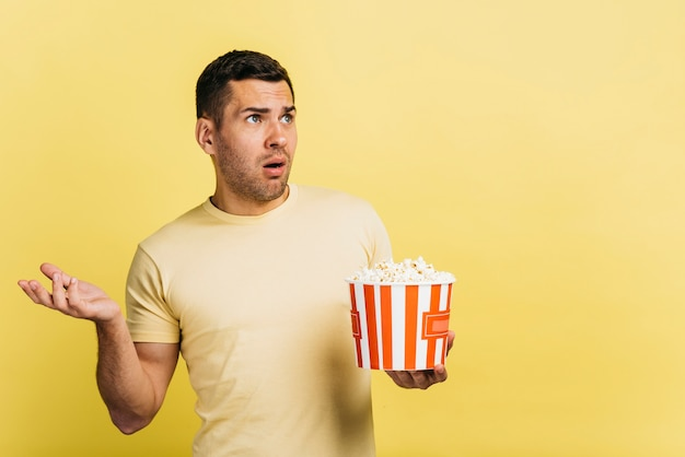 Confused man eating popcorn with copy space