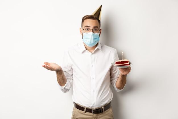 Uomo confuso in maschera facciale, tenendo la torta di compleanno e alzando le spalle, in piedi su sfondo bianco all'oscuro.