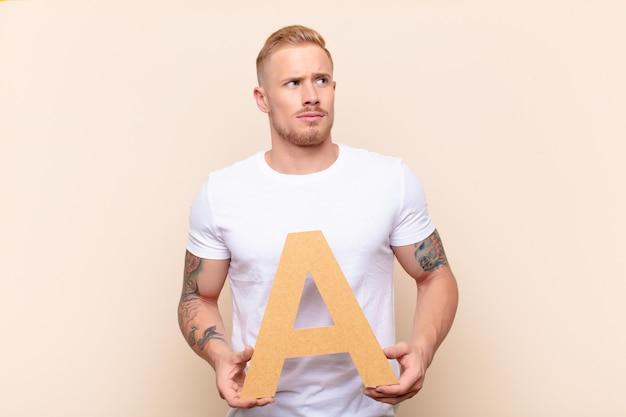Путать мужчина держит букву а алфавита, чтобы сформировать слово