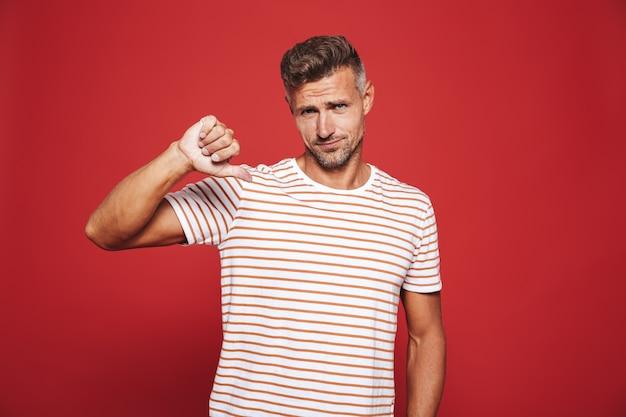 Смущенный мужчина в полосатой футболке показывает большой палец вниз и выражает неприязнь, изолированную на красном