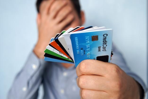 多くのクレジットカードを見て混乱している人は、青い背景でどれを選択するかわからない。若い男は物思いにふけるポーズでクレジットカードとデビットカードの停止を保持しています。男は支払うカードを選択します