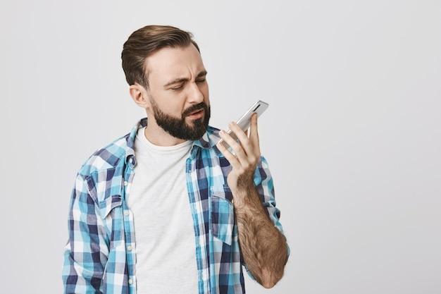 Uomo confuso che esamina il telefono cellulare dopo la chiamata terminata