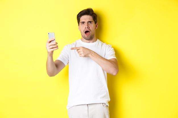 휴대 전화 화면에서 손가락을 가리키는 혼란스러운 남자, 노란색 배경 위에 서서 무언가를 이해할 수 없음