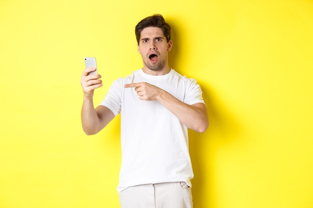 Confused man pointing finger at mobile phone screen, cant understand something, standing over yellow background. copy space