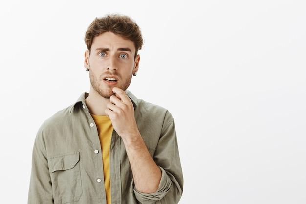 Confused man posing in the studio
