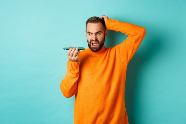 Confused man scratching head while talking on speakerphone, record voice message with indecisive face, standing in orange sweater over light turquoise wall.