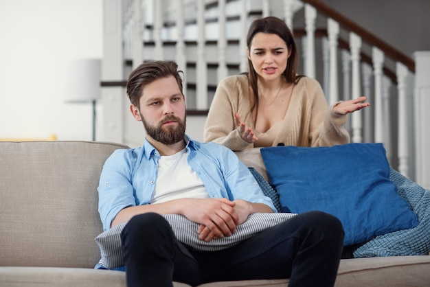 Confused man sits on the couch while his girlfriend yells and quarrels with him at home. big family problems.
