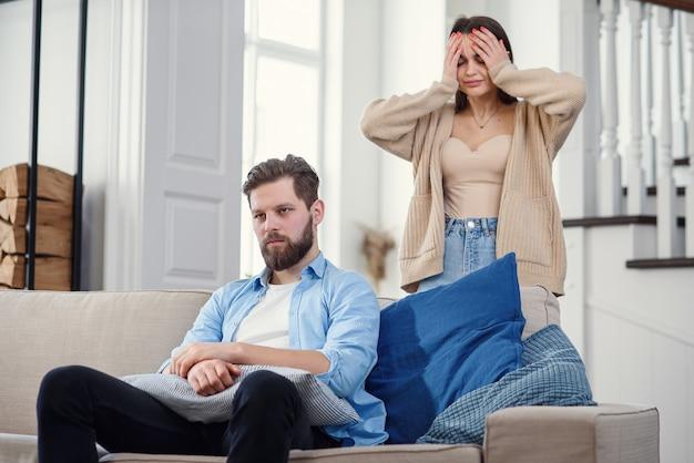 Смущенный мужчина сидит на диване, а его девушка кричит и ругается с ним дома. большие семейные проблемы.
