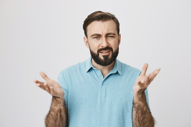 Confused man squinting and spread hands sideways questioned