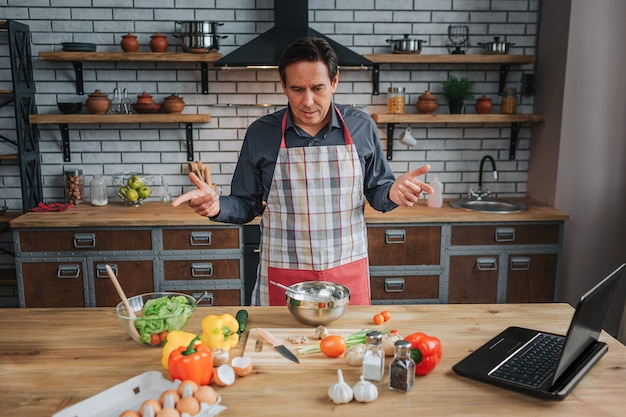 Confused man stand at table in kitchen. he look at colorful vegetables on desk. man wear apron.