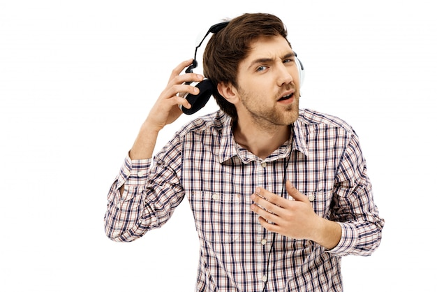 Confused man take-off headphones to answer question