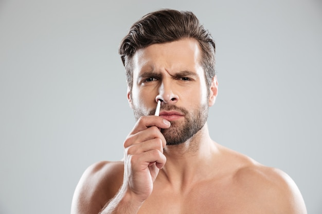 Confused man trying to tweezer hair in nose