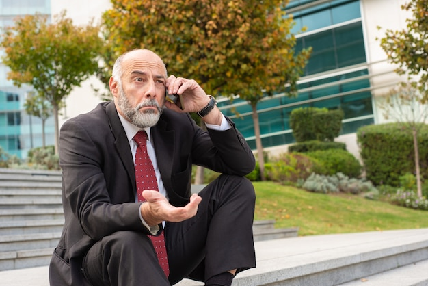 Confused mature business leader speaking on cell