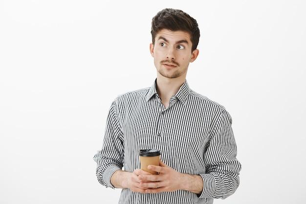 Смущенный зрелый европейский парень с усами и бородой, смотрит в сторону, приподняв брови, пьет кофе и его спрашивают о поведении друга, думая, что он странный из-за серой стены