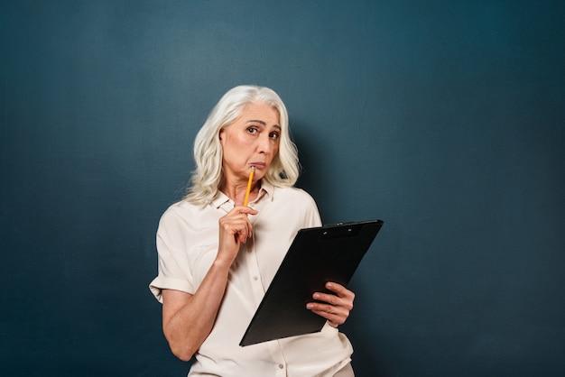 成熟した古い女性がクリップボードにメモを書いて混乱しています。