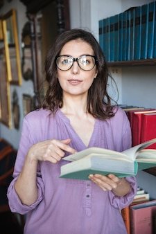 Confused mature woman in eyeglasses pointing finger at book