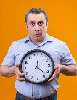 Confused middle age man in blue striped shirt holding wall clock showing time
