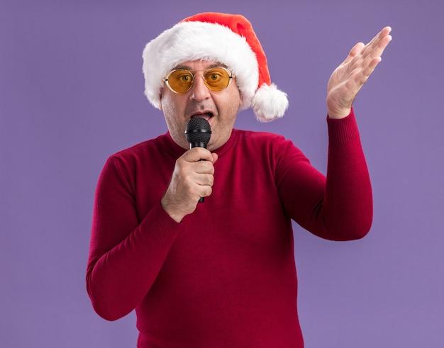 紫色の背景の上に立って腕を上げてマイクに向かって話している黄色いメガネでクリスマスサンタの帽子をかぶって混乱した中年男性