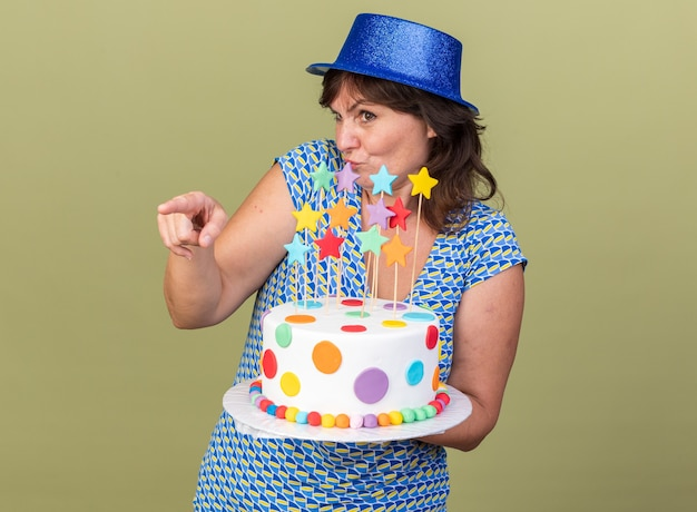 Confused middle age woman in party hat holding birthday cake looking aside pointing with index finger to the side celebrating birthday party standing over green wall