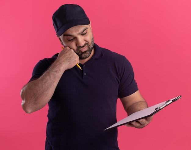 분홍색 벽에 고립 된 뺨에 주먹을 넣어 클립 보드를 들고 유니폼과 모자에 혼란 중년 배달 남자