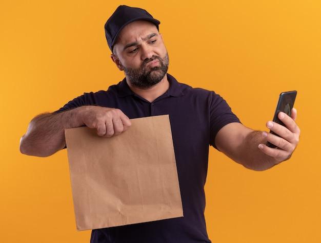Uomo di consegna di mezza età confuso in uniforme e cappuccio che tiene il pacchetto di cibo di carta e che guarda il telefono in mano isolato sulla parete gialla