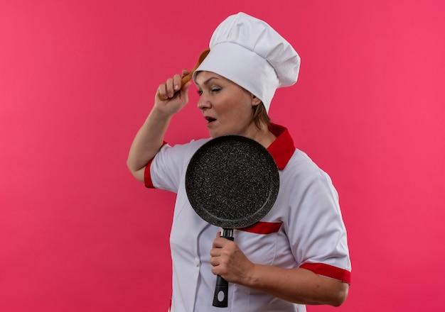 Il cuoco femminile di mezza età confuso in padella della tenuta dell'uniforme del cuoco unico ha messo il cucchiaio nella sua fronte sulla parete rosa isolata
